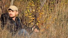 Repos de voyageur se reposant au sol parmi l'herbe sèche dans les derniers rayons du soleil chaud d'octobre clips vidéos