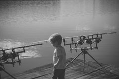 Repos en voyage de pêche Petit garçon avec les cannes à pêche sur le pilier Image libre de droits