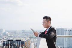 Repos formel habill? par jeune homme au balcon de bureau photo stock