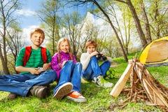 Repos heureux de trois amis ensemble pendant le camping Image libre de droits