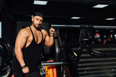 Repos modèle de grande forme physique d'homme fort dans le gymnase penché contre l'équipement de sport de simulateur Photo libre de droits