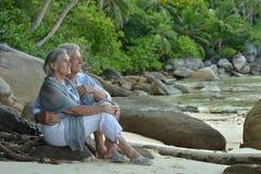 Repos plus âgé de couples à la plage tropicale Photographie stock libre de droits