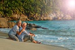 Repos plus âgé de couples à la plage tropicale Photos libres de droits