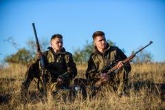 Repos pour le vrai concept d'hommes Discussion du crochet Chasseurs avec des fusils détendant dans l'environnement de nature L'am image stock