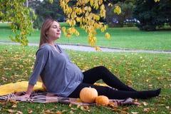 Repos pour les mères enceintes La belle jeune femme enceinte s'asseyant sur l'herbe en parc dans la pose de lotus faisant la resp Photo stock