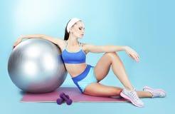 repose Idrottskvinna med sportutrustning - en konditionboll och hantlar royaltyfria bilder