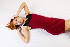 Reposer américain asiatique maigre sur la robe rouge de plancher Photos libres de droits