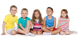 Reposer cinq enfants gais Photographie stock