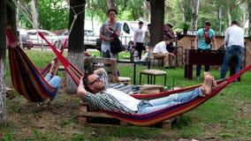 Reposez-vous en parc, un homme balançant dans un attachement d'hamac à un arbre sur le fond des personnes jouant le football de t clips vidéos