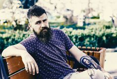 Reposez-vous et détendez le concept Homme barbu avec la coupe de cheveux fraîche détendant, fond urbain Le hippie apprécient le j Photo libre de droits
