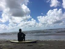 Reposez-vous sur la planche de surf par le bord de la mer photo libre de droits