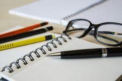 Repräsentativstift, der auf ein leeres Anmerkungsbuch mit Bleistiften und Gläsern auf Tabelle legt Neigungs-obengroßaufnahme Lizenzfreies Stockfoto
