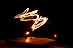 Représentation de jonglerie du feu d'artiste de rue La peinture légère et la longue photo d'exposition à la forme traîne Île de p images stock