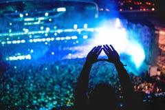 Représentation de l'amour au concert, silhouette des mains faisant des gestes avec le fond de lumières Image libre de droits