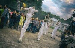Représentation de rue de soirée Cortège des femmes sur des échasses avec des masques de gaz dans la fumée L'orientation diagonale photos stock