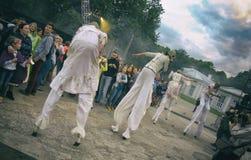 Représentation de rue de soirée Cortège des femmes sur des échasses avec des masques de gaz dans la fumée L'orientation diagonale images libres de droits