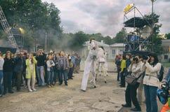 Représentation de rue de soirée Femmes sur des échasses avec des masques de gaz dans la fumée Film stylisé photographie stock