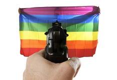 Représentation violente d'intolérance d'attaque terroriste avec la main dirigeant l'arme à feu sur le drapeau se tenant gai fier photographie stock libre de droits