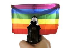 Représentation violente d'intolérance d'attaque terroriste avec la main dirigeant l'arme à feu sur le drapeau se tenant gai fier photo libre de droits