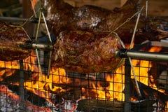 Repreensão do cuspe da carne sobre as chamas de um fogo de log foto de stock