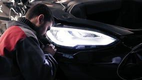Represantative Autocenter vastmakend een plastic stuk van auto` s bumper aan de bodemkant stock video