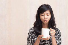Beautiful asian girl blowing a hot beverage Stock Images