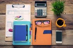 Representação gráfica, calculadoras, cadernos, penas, copo de café e monóculos no assoalho de madeira fotos de stock royalty free