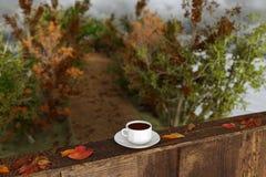 representación 3d de la taza de café en alféizar de madera con las hojas i Foto de archivo