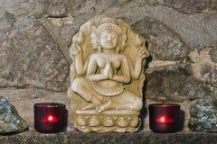 Representación de Buda, talla de piedra, con las velas y las flores, Tailandia Imagen de archivo libre de regalías