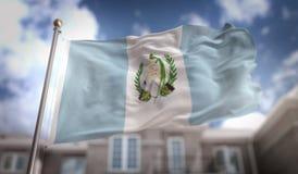Representación de la bandera 3D de Guatemala en fondo del edificio del cielo azul Fotos de archivo libres de regalías