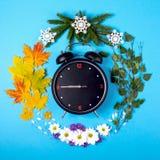 Representación de las estaciones del año a través del despertador y Imagen de archivo libre de regalías
