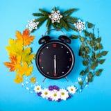 Representación de las estaciones del año a través del despertador y Imagenes de archivo