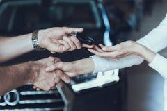 Representant Give Car Keys till kvinnlign Lucky Owner arkivfoton
