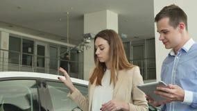 Representant- och kvinnasamtalen om bilen i bilåterförsäljare arkivfilmer
