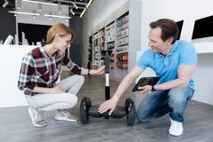 Representant som fritt hjälper den unga kvinnliga kunden med sparkcykeln för händer Royaltyfri Bild