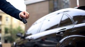Representant som ger biltangent till köparen, återförsäljarevisningslokal, automatiskhyra, lyx royaltyfria bilder