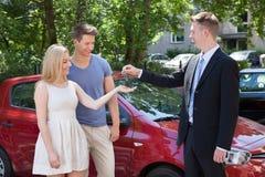 Representant som ger tangent till par med bilen Royaltyfri Fotografi