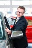 Representant som säljer bilen på återförsäljaren Fotografering för Bildbyråer