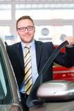 Representant som säljer bilen på återförsäljaren Royaltyfria Bilder