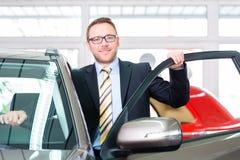Representant som säljer bilen på återförsäljaren Arkivbilder
