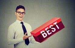Representantaffärsman som annonserar hans bästa produkt i en stor röd ask arkivbild