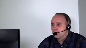 Representante/delegado de servicio de atención al cliente masculino confiado con las auriculares delante del ordenador almacen de video