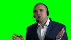 Representante/delegado de servicio de atención al cliente masculino confiado con las auriculares en centro de atención telefónica metrajes
