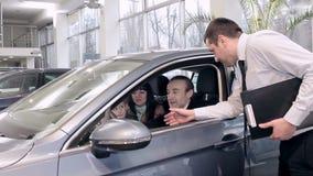 Representanten övertygar par för att köpa den nya bilen arkivfilmer