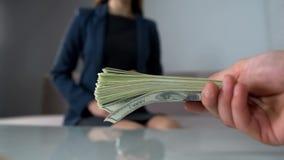 Representanten erbjuder pengar till damen i dräkten, bestickning och den olagliga affären, korruption arkivfoto