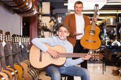 Representanten råder en gitarrköpare Arkivbilder