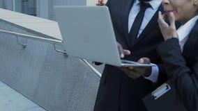 Representantes de la empresa de la construcción que realizan cambios a los documentos en el ordenador portátil almacen de metraje de vídeo