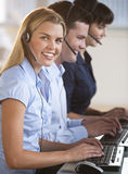 Representantes do serviço de atenção a o cliente em computadores Fotografia de Stock Royalty Free