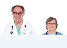 Representantes médicos con el anuncio en blanco de la bandera Imagen de archivo libre de regalías