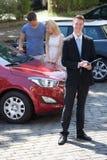 Representanthandstil på skrivplattan med par som ser bilen royaltyfri fotografi